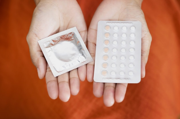 Woman is using birth control pills and condoms. before having sex with your boyfriend every time to prevent pregnancy.