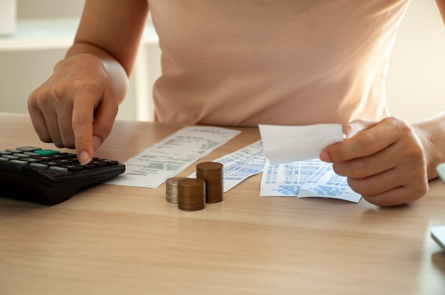 Woman is using a calculator to calculate expenses with invoices placed on the table