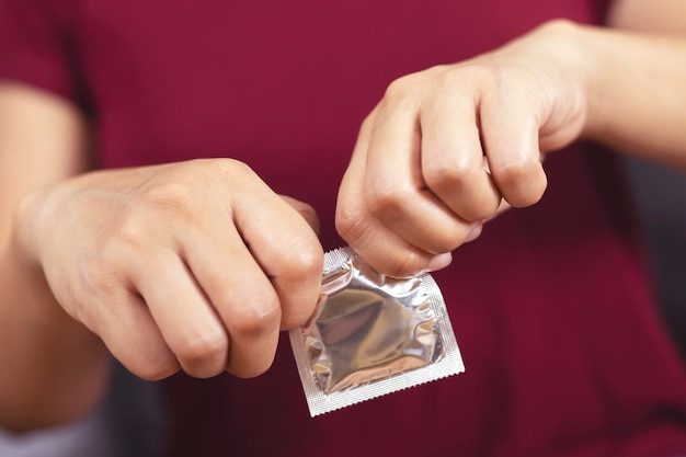 Woman is using condom to prevent aids.