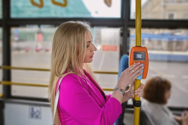 여자는 대중 교통에서 요금을 지불하기 위해 비접촉 결제 단말기를 사용하고 있습니다.