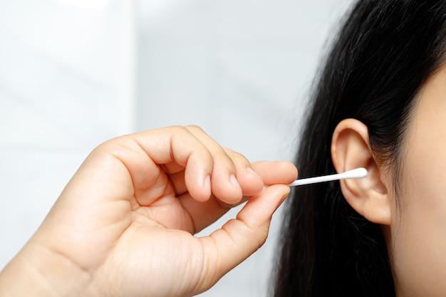 女性は綿棒を使用して耳をきれいにします