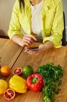 여자는 smarthone을 사용하고 레시피를 찾고 있습니다.