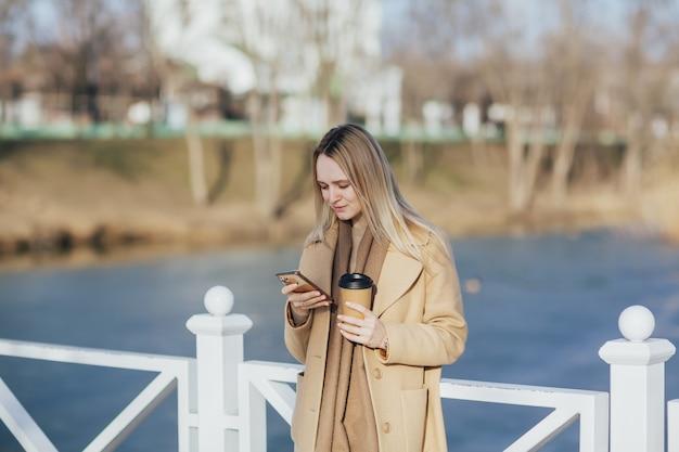 女性はスマートフォンを使用してコーヒーを持っています