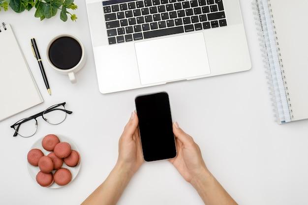 女性はラップトップで白いオフィスの机のテーブルの上に空白の画面でスマートフォンを使用しています