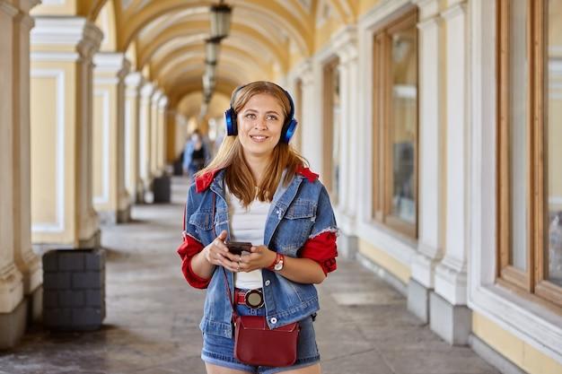 여자는 아치형 무역 갤러리에서 전화로 이야기하기 위해 무선 헤드폰을 사용하고 있습니다.
