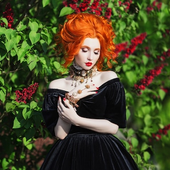 A woman is a vampire with pale skin and red hair in a black dress and a necklace on her neck against the background of nature. girl witch with vampire claws and red lips.