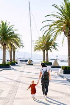 女性はボートの桟橋でヤシの木の中で彼女の2歳の娘と手をつないで歩いています。