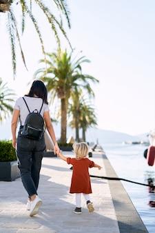 女性はボートの桟橋のヤシの木のそばで幼児と手をつないで歩いています。