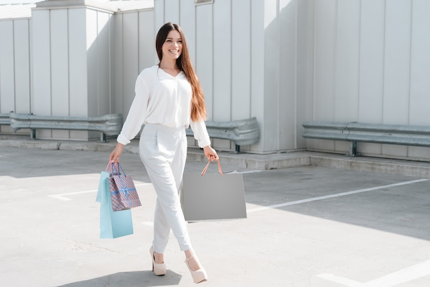 Woman is walking on road near parking after shopping in mall