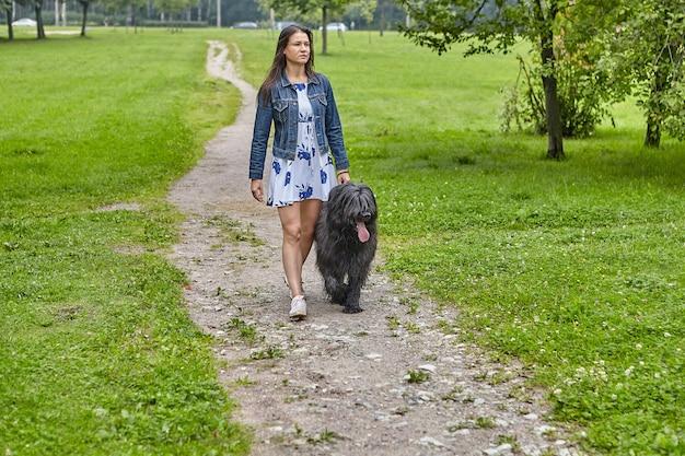 여자는 낮에 공개 부분에서 검은 브리아 드와 함께 걷고 있습니다.