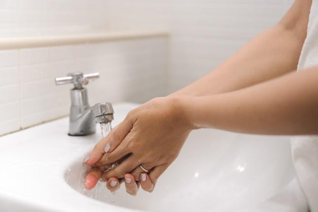 Woman is washing her hand under running water in bathroom.