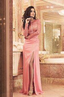 Woman is wearing pink dress in the luxury bathroom