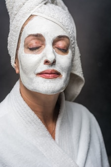Woman is white clay on his face mask