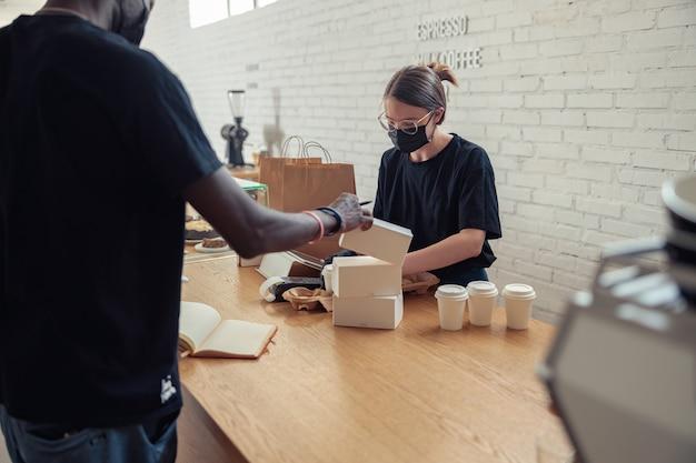 여자는 covid에서 커피 하우스에서 일하고 있다