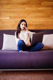 女性はラップトップに取り組んでおり、家のベッドの上に座って電話で話しています。