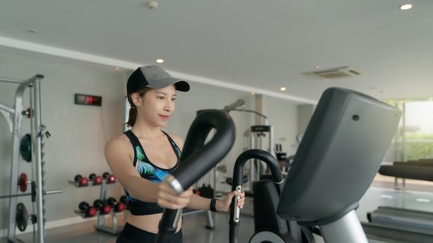 Женщина работает в тренажерном зале. занимаюсь кардиотренировками на эллиптическом тренажере по фитнесу.