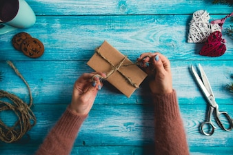 Woman is wrapping christmas presents on blue wooden table