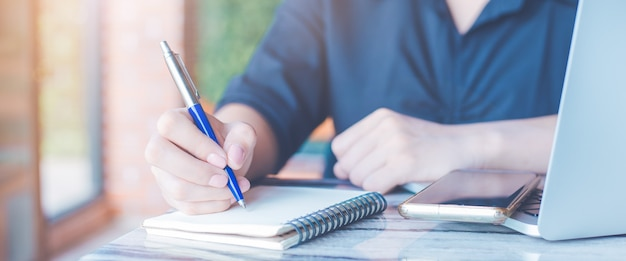 Woman is writing on a notebook with a pen in the office.on the table there are mobile phones and laptop computers.web banner.