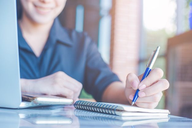 Woman is writing on a notebook with a pen and she is using a mobile phone in the office.
