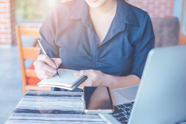 Женщина пишет на блокноте ручкой, и она использует мобильный телефон и компьютерный ноутбук в офисе.