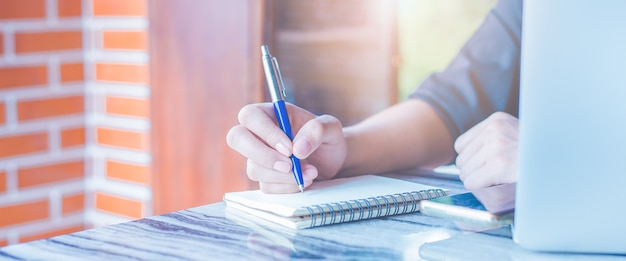 女性はペンでノートに書いていて、彼女はoffice.webバナーで携帯電話を使用しています。