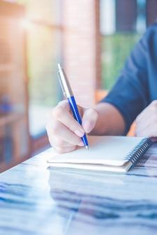 여자는 사무실에서 펜으로 노트북에 글을 쓰고 있습니다.
