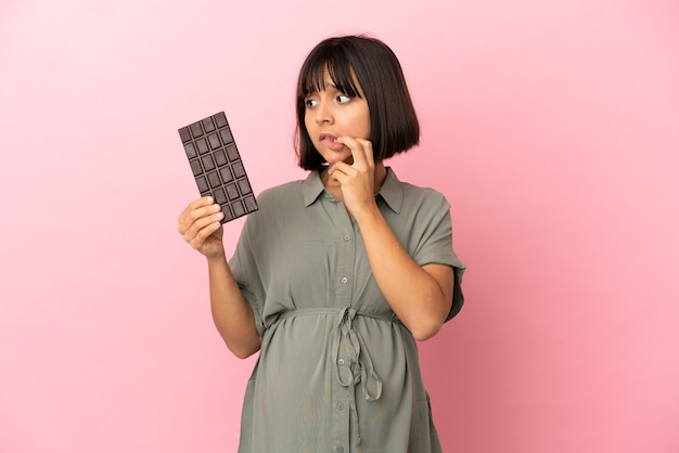 Woman over isolated background pregnant and having doubts while holding chocolate