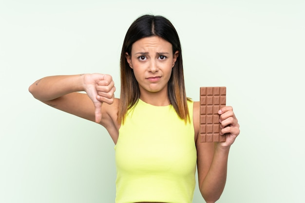 Woman over isolated green wall taking a chocolate tablet making bad signal