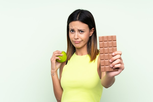 Woman over isolated green wall taking a chocolate tablet in one hand and an apple in the other
