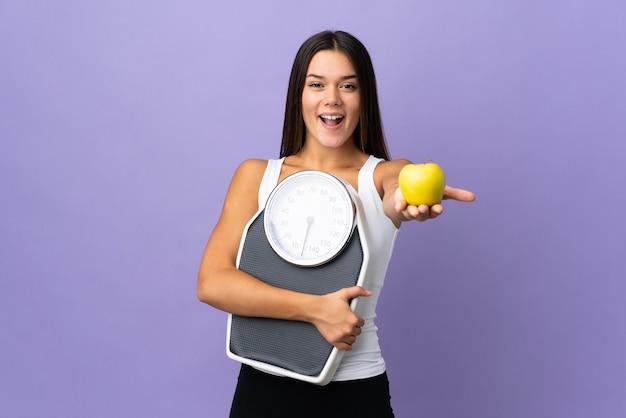 Женщина изолирована на фиолетовом, держа весы и предлагая яблоко