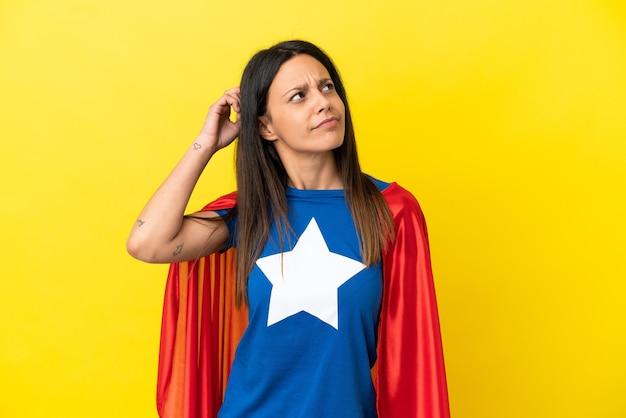 Женщина изолирована на желтом фоне в костюме супергероя и сомневается