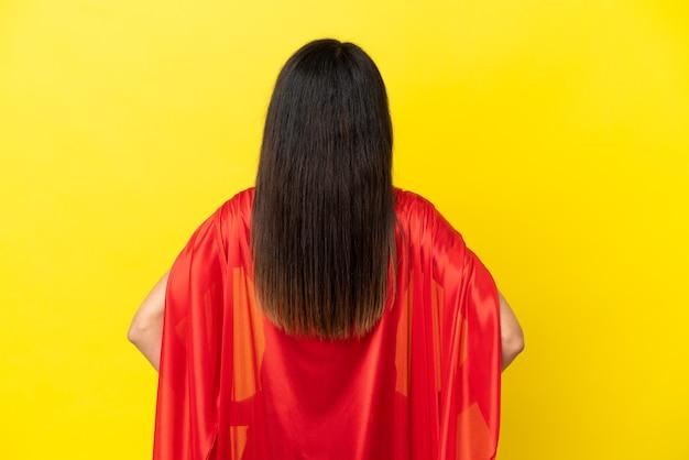 Женщина изолирована на желтом фоне в костюме супергероя в заднем положении