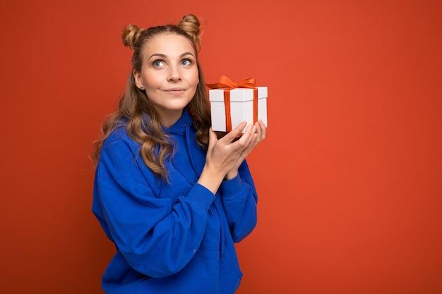 선물 상자를 들고 측면을 찾고 세련 된 캐주얼 옷을 입고 화려한 배경 벽 위에 절연하는 여자. 공간 복사