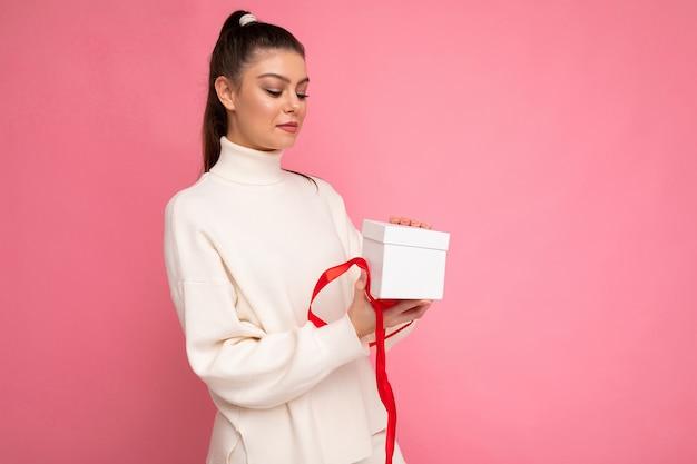 カラフルな背景の壁に隔離された女性は、ギフトボックスを保持し、横を見てスタイリッシュなカジュアルな服を着ています。