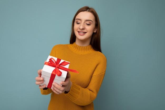 유행 옷을 입고 화려한 벽에 고립 된 여자 선물 상자를 들고 빨간 리본으로 선물 상자를보고.
