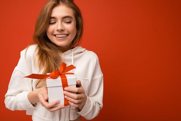 빨간 리본 흰색 선물 상자를 들고 재미 흰색 까마귀를 입고 오렌지 벽 위에 절연하는 여자. 빈 공간