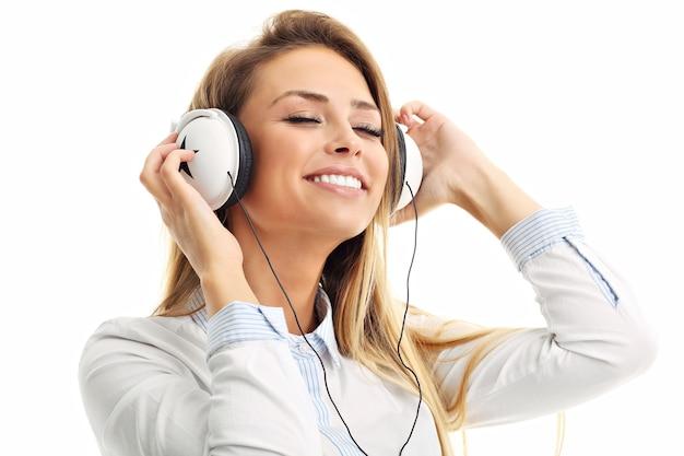Женщина изолирована над белой с наушниками, слушает музыку