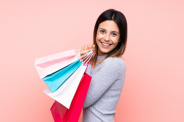 Woman over isolated pink wall holding shopping bags and smiling