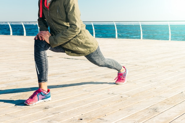 Woman in jacket, hood and sneakers doing stretching on the beach