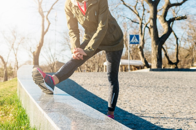 Woman in jacket and sneakers does sports exercises in a park in the morning