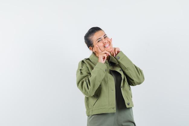 Donna in giacca, t-shirt tenendo le dita sulle guance e sembra carina