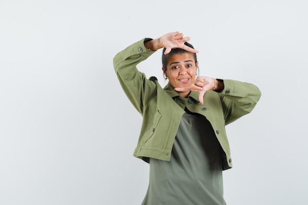 Donna in giacca, t-shirt che fa il gesto del telaio e sembra vivace