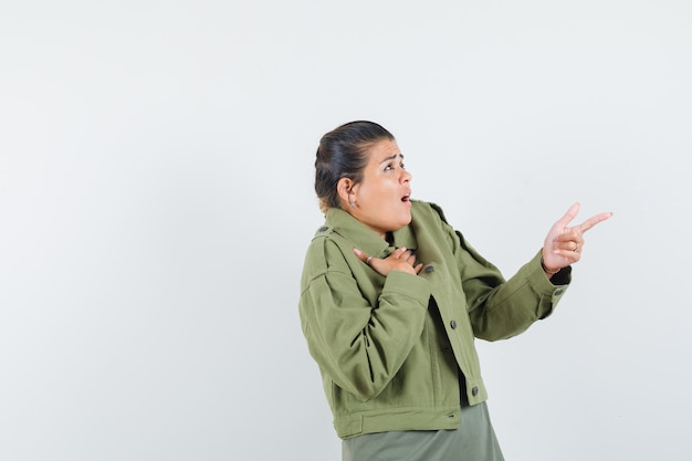 Woman in jacket, t-shirt pointing away and looking scared