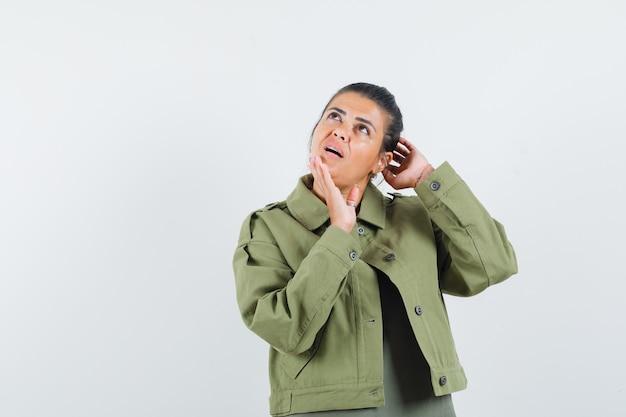 Donna in giacca, t-shirt in posa stando in piedi e guardando pensieroso