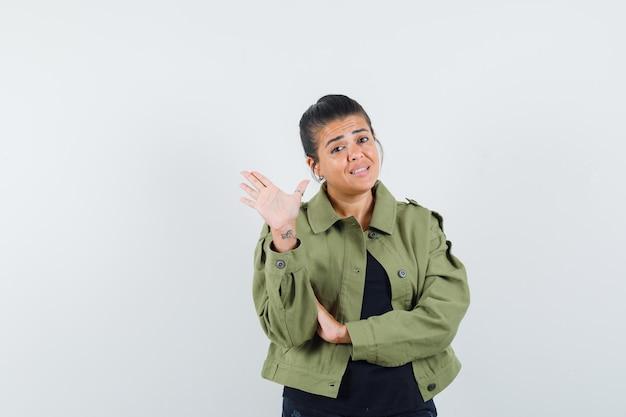 Donna in giacca, t-shirt che mostra cinque dita e sembra sicura