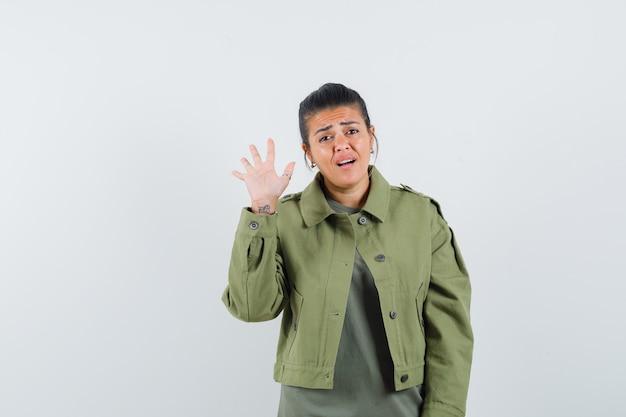 Donna in giacca, t-shirt che mostra cinque dita e che sembra preoccupata