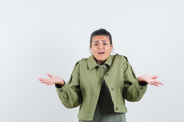 Donna in giacca, t-shirt che mostra gesto impotente e che sembra confusa
