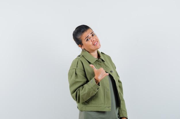 Donna in giacca, t-shirt che mostra il pollice in su e che sembra esitante