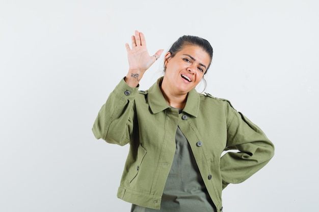 Woman in jacket, t-shirt waving hand for greeting and looking cheerful