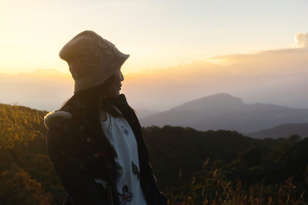 Woman jacket traveling on a cold morning sun mountain